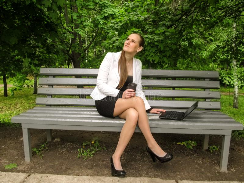 Μια νέα γυναίκα κρατά ένα ποτήρι του καφέ στο χέρι της και ανατρέχει καθμένος σε έναν πάγκο με τα πόδια της που διασχίζονται r στοκ εικόνες