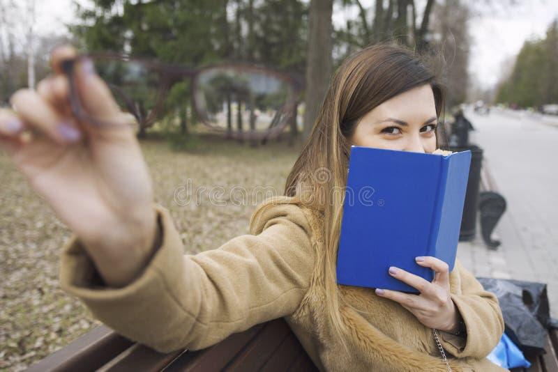 Μια νέα γυναίκα κρατά τα γυαλιά διαθέσιμα και το βιβλίο - συνεδρίαση στον πάγκο στο πάρκο στοκ εικόνες