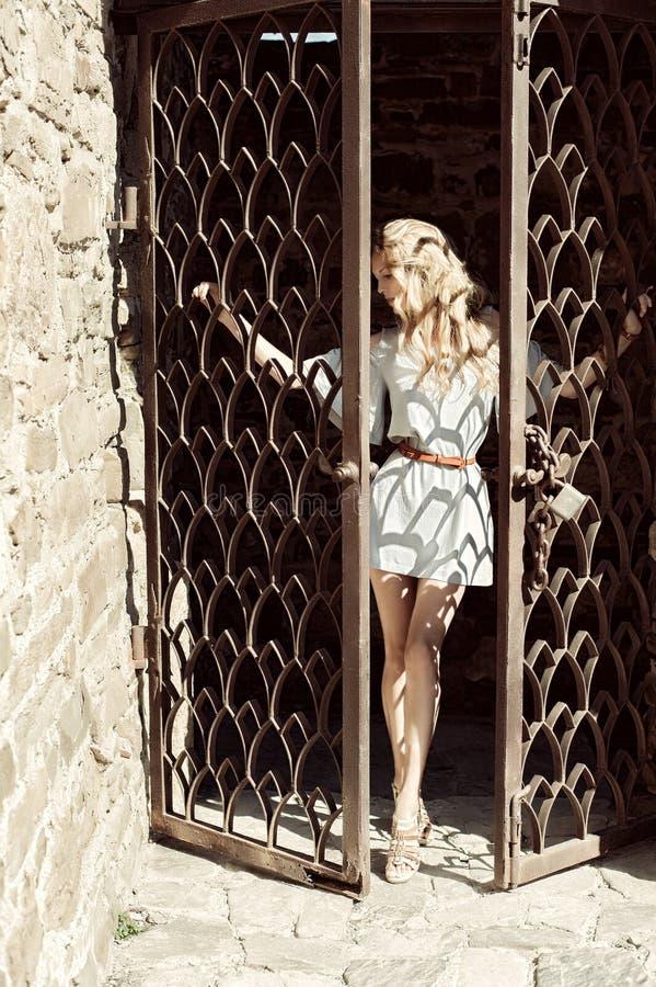 Μια νέα γυναίκα κρατά τα χέρια της πίσω από τους φραγμούς η πόρτα στοκ εικόνες