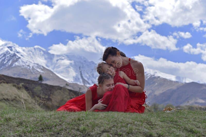 Μια νέα γυναίκα με δύο κόρες στο κόκκινο ντύνει να στηριχτεί στα χιονοσκεπή βουνά την άνοιξη στοκ φωτογραφία