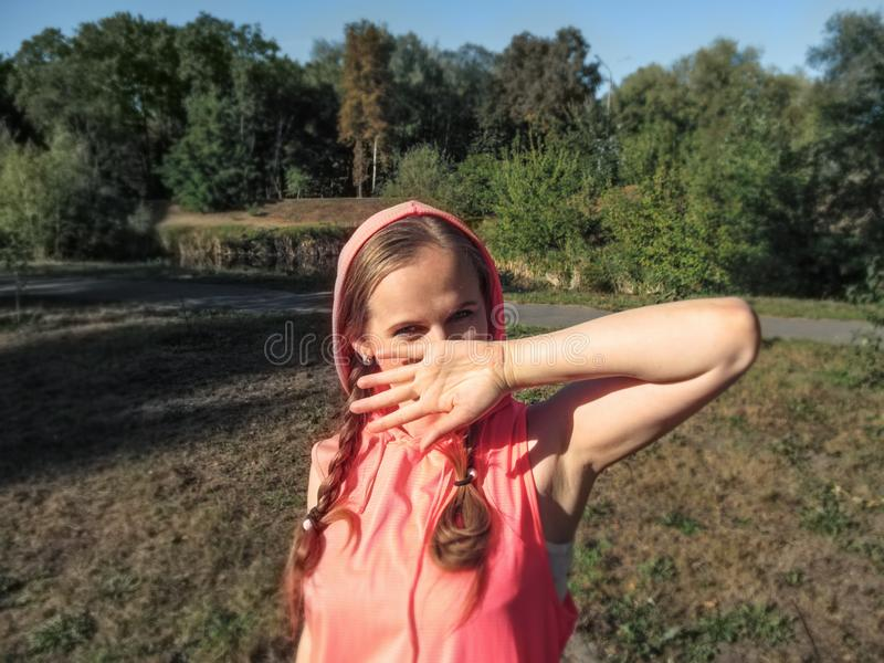 Μια νέα γυναίκα με μια εύθυμη έκφραση των ματιών καλύπτει το πρόσωπό της με το χέρι της Πτώση ακτίνων ήλιων σε ετοιμότητα το πρόσ στοκ εικόνες με δικαίωμα ελεύθερης χρήσης