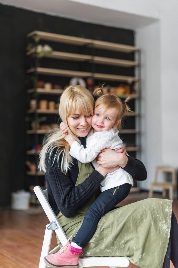 Μια νέα γυναίκα με μια μικρή κόρη που χαλαρώνει στο δημιουργικό στούντιο Μητέρα και η μικρή συνεδρίαση παιδιών της στην καρέκλα στοκ εικόνα με δικαίωμα ελεύθερης χρήσης