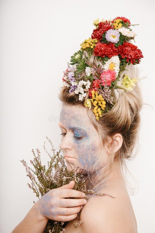 Μια νέα γυναίκα με τα λουλούδια σε ετοιμότητα το κεφάλι και της Εικόνα άνοιξη με τα λουλούδια Άτομο με ζωηρόχρωμες εγκαταστάσεις  στοκ εικόνα με δικαίωμα ελεύθερης χρήσης