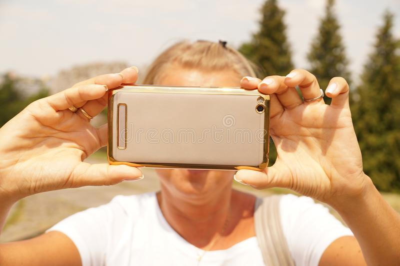 Μια νέα γυναίκα παίρνει μια εικόνα με ένα smartphone στοκ εικόνα με δικαίωμα ελεύθερης χρήσης