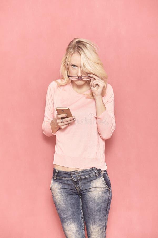 Μια νέα γυναίκα που αναμένει με ενδιαφέρον τη κάμερα, που κρατά το έξυπνο τηλέφωνο στο χέρι της στοκ εικόνα