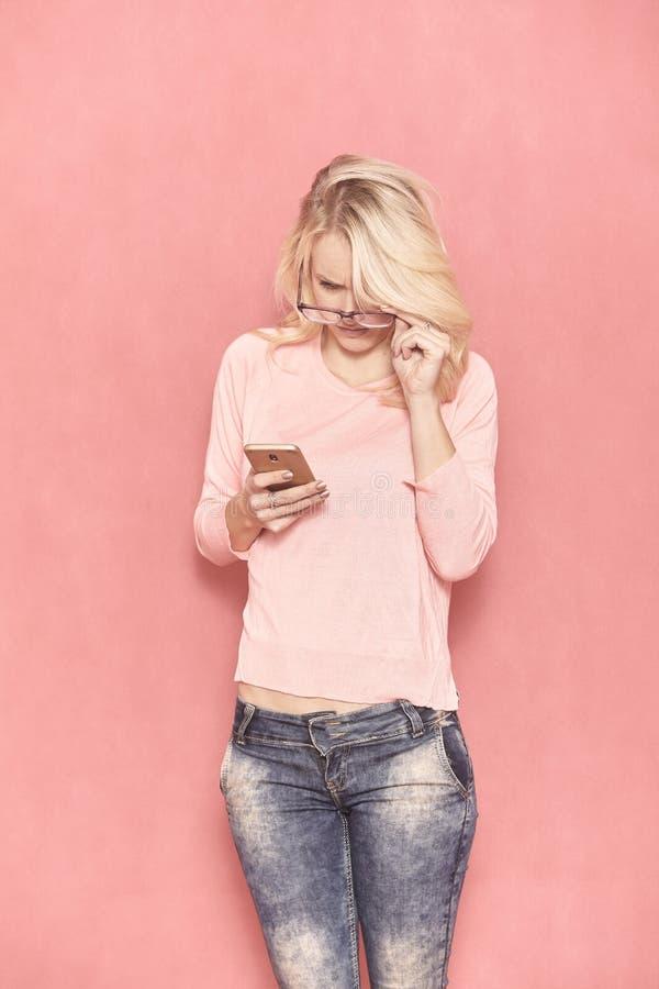 Μια νέα γυναίκα που κοιτάζει στο έξυπνο τηλέφωνό της με eyeglasses της, στοκ εικόνες με δικαίωμα ελεύθερης χρήσης