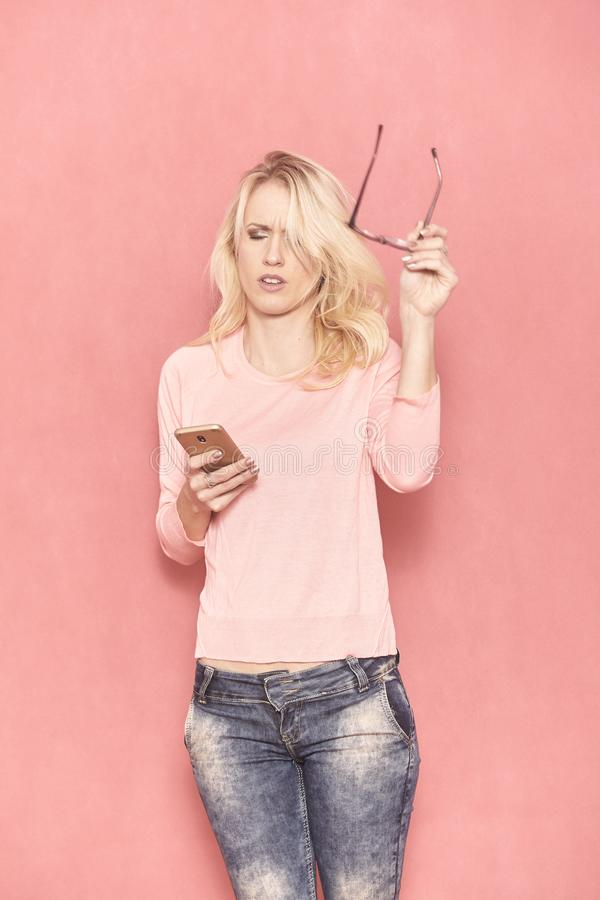 Μια νέα γυναίκα που κουράζεται χρησιμοποιώντας το smartphone της, 20-29 χρονών, μακριά ξανθά μαλλιά στοκ εικόνες