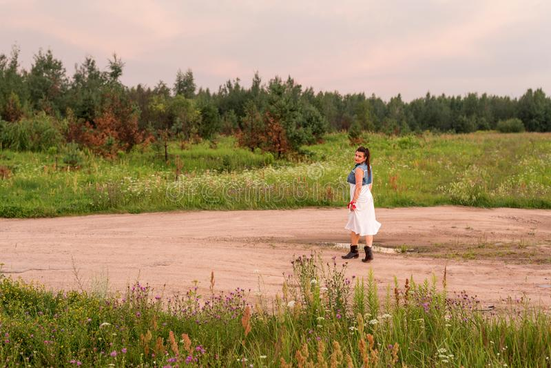 Μια νέα γυναίκα που περπατά κατά μήκος του δρόμου στο ηλιοβασίλεμα το βράδυ στοκ εικόνα