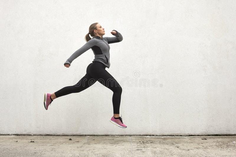 Μια νέα γυναίκα, που πηδά στον αέρα, υπαίθρια, τον άσπρο τοίχο πίσω, απλός minimalistic, αθλητικά ενδύματα στοκ φωτογραφίες