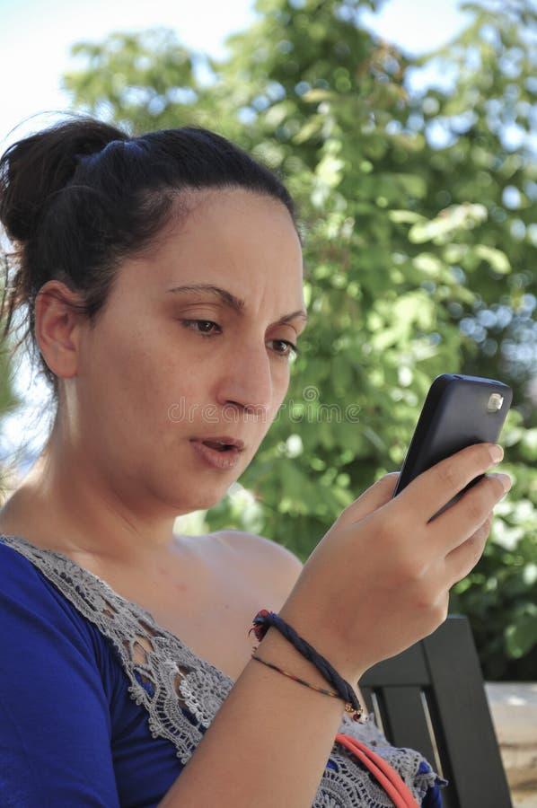 Μια νέα γυναίκα που φαίνεται κάτι σε ένα έξυπνο τηλέφωνο στοκ εικόνα