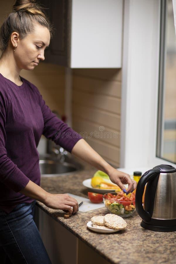 Μια νέα γυναίκα προετοιμάζει μια σαλάτα στοκ φωτογραφία με δικαίωμα ελεύθερης χρήσης
