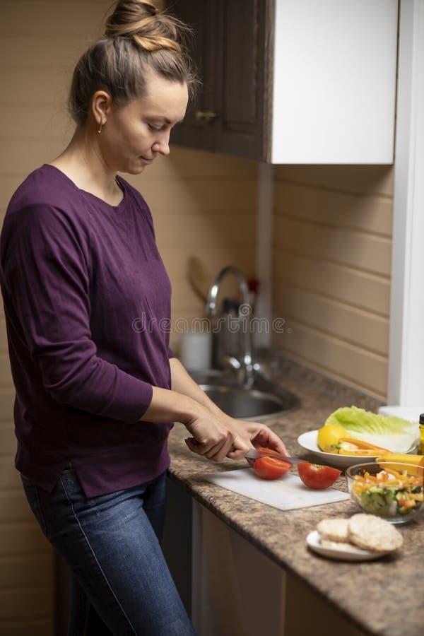 Μια νέα γυναίκα προετοιμάζει μια σαλάτα στοκ φωτογραφία