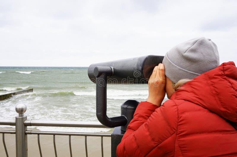 Μια νέα γυναίκα σε ένα κόκκινο σακάκι και μια πλεκτή ΚΑΠ εξετάζει με το ενδιαφέρον μέσω ενός τηλεσκοπίου τη θάλασσα με τα κύματα, στοκ φωτογραφίες