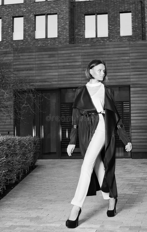 Μια νέα γυναίκα σε ένα όμορφο μαύρο παλτό και ένα άσπρο παντελόνι που περπατούν κάτω από την οδό στοκ φωτογραφίες με δικαίωμα ελεύθερης χρήσης