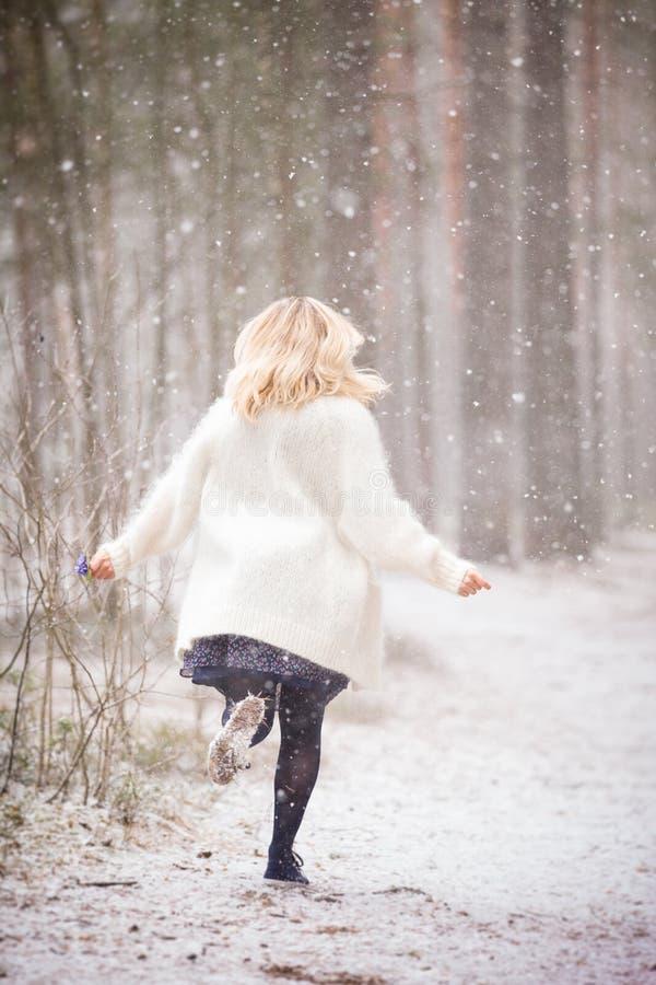 Μια νέα γυναίκα σε μια άσπρη θερμή ζακέτα που τρέχει σε ένα δάσος και που κρατά μια δέσμη του πρώτου μπλε άνοιξη ανθίζει στοκ φωτογραφία