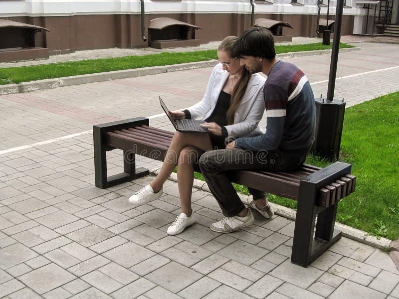 Μια νέα γυναίκα στα γυαλιά παρουσιάζει κάτι σε έναν άνδρα σε μια οθόνη lap-top καθμένος σε έναν πάγκο υπαίθρια Νέα ενήλικη εργασί στοκ φωτογραφία
