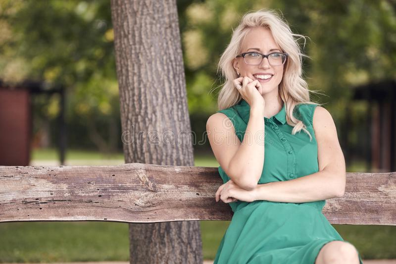 Μια νέα γυναίκα, 25 χρονών, που κάθεται στον ξύλινο πάγκο στο πάρκο, πράσινο φόρεμα, ευτυχές θετικό πορτρέτο στοκ εικόνες