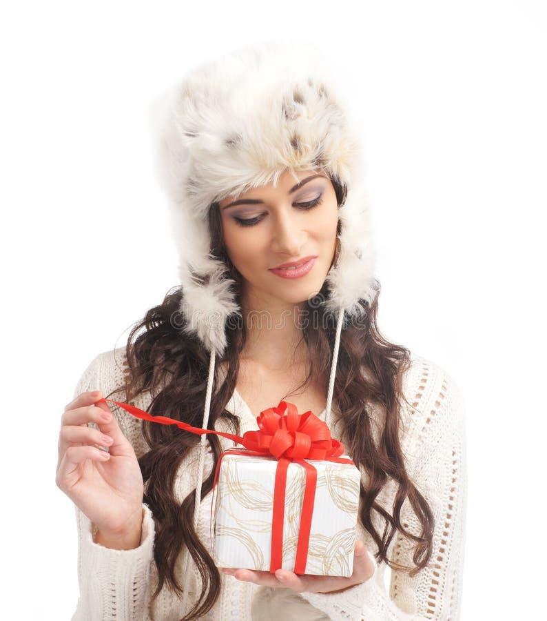 Μια νέα γυναίκα brunette που ανοίγει ένα χριστουγεννιάτικο δώρο στοκ φωτογραφία