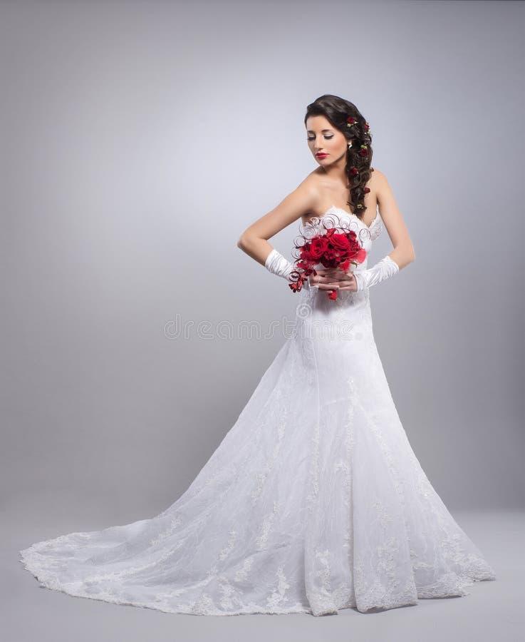 Μια νέα γυναίκα brunette σε ένα άσπρο νυφικό φόρεμα στοκ εικόνες