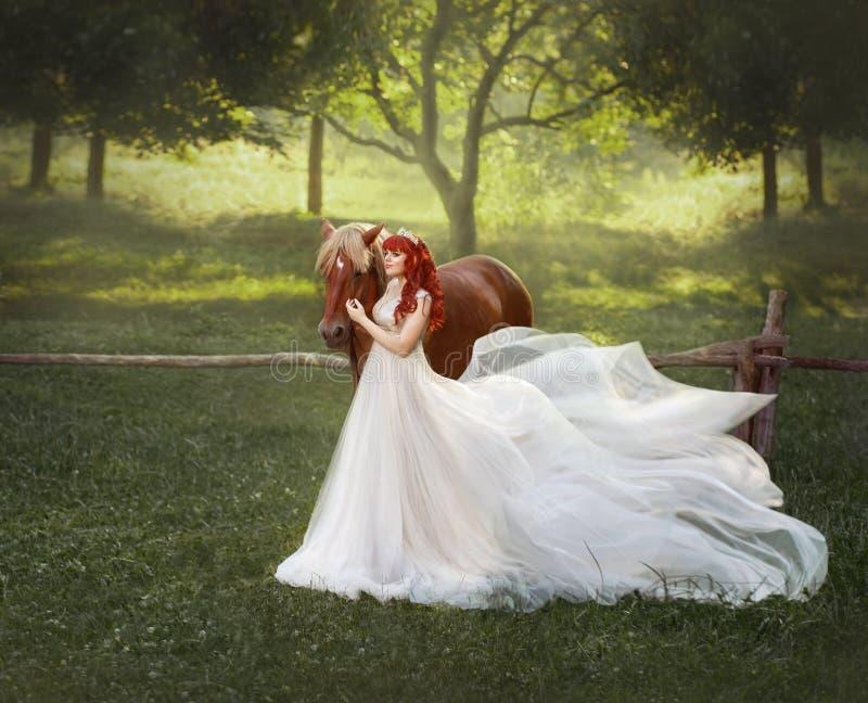 Μια νέα, κοκκινομάλλης πριγκήπισσα σε μια τιάρα κρυστάλλου, αγκαλιάσματα και κτυπήματα το άλογό της Το υπόβαθρο είναι ένα φανταστ στοκ φωτογραφίες
