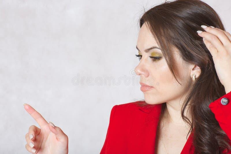 Μια νέα κομψή γυναίκα σε ένα κόκκινο σακάκι στοκ φωτογραφίες