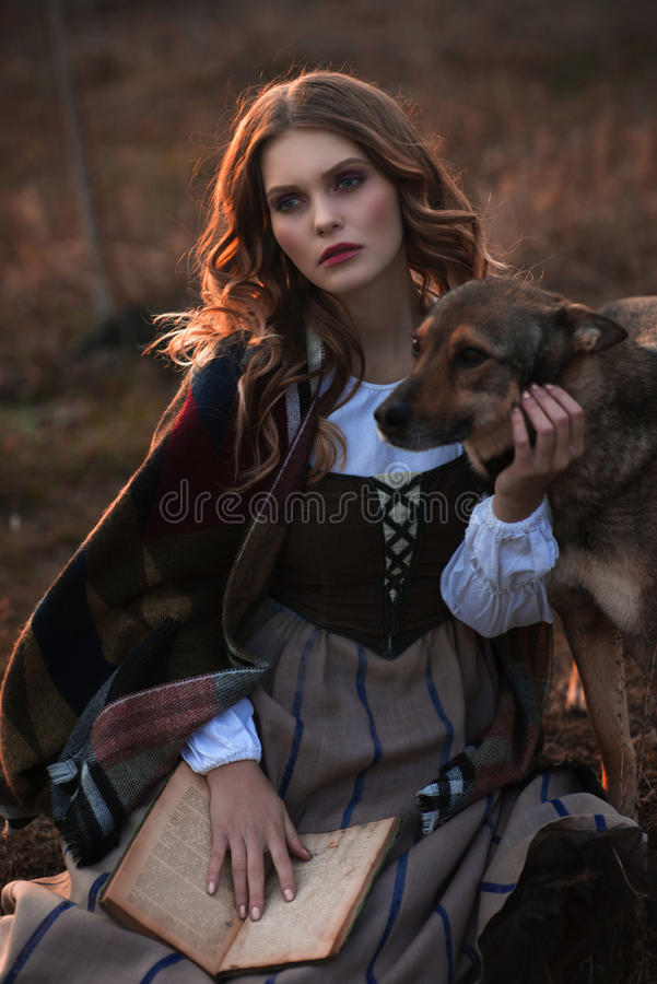Μια νέα κυρία σε ένα μεσαιωνικό φόρεμα με ένα σκυλί και ένα βιβλίο στοκ εικόνες