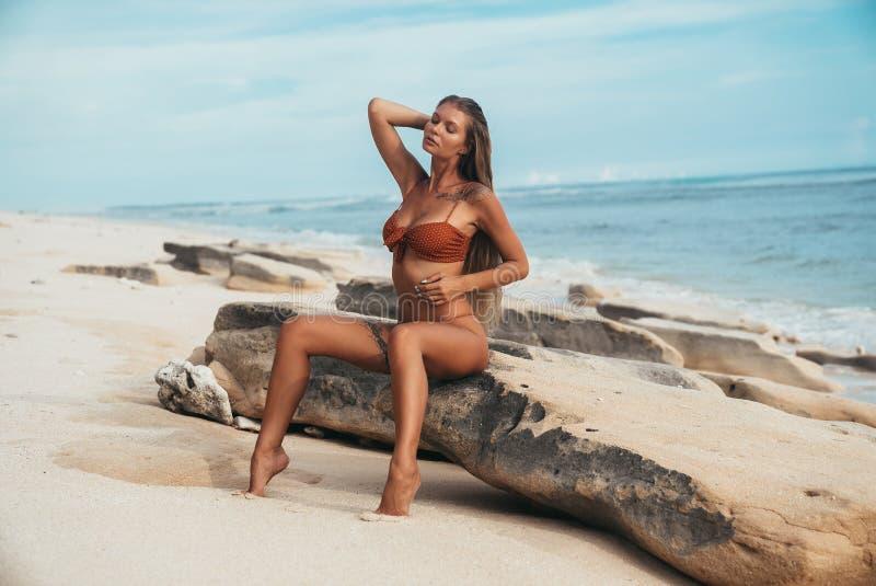 Μια νέα λεπτή όμορφη πρότυπη στήριξη γυναικών στην παραλία, που κτυπά την κομψή μακριά άσπρη τρίχα της με το χέρι της λεπτός στοκ εικόνες