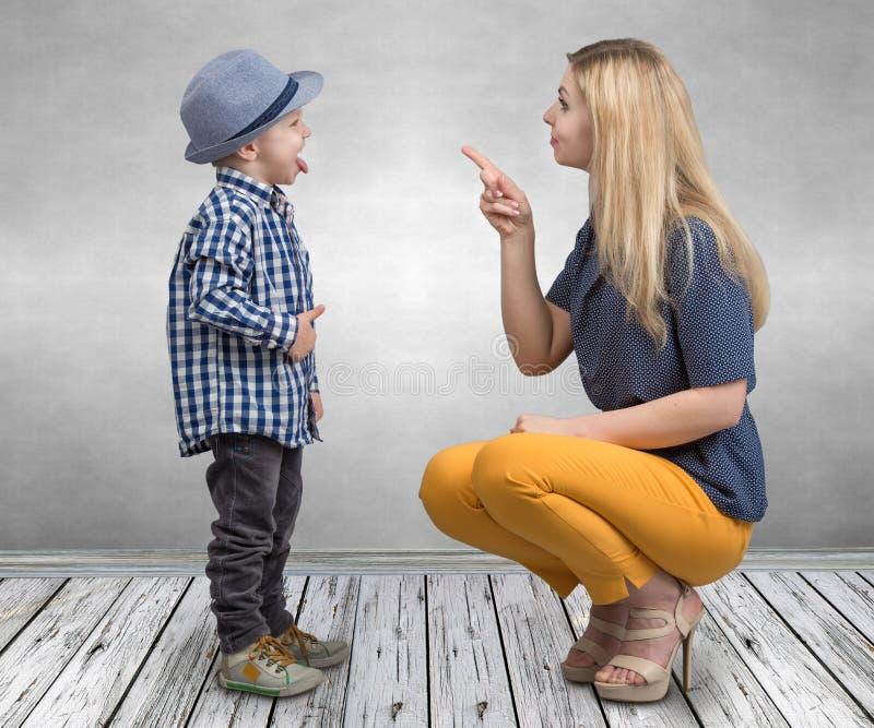 Μια νέα μητέρα επιπλήττει τον άτακτο μικρό γιο της Το αγόρι που παρουσιάζει γλώσσα και πειράζει mom στοκ εικόνα