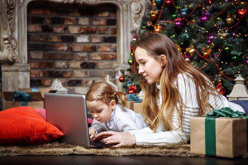 Μια νέα μητέρα και η κόρη της που χρησιμοποιούν ένα lap-top που βρίσκεται κοντά στο χριστουγεννιάτικο δέντρο στοκ φωτογραφίες