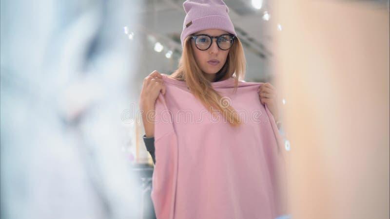Μια νέα μοντέρνη γυναίκα hipster στα μοντέρνα γυαλιά και ένα καπέλο προσπαθεί στα νέα ενδύματα στο κατάστημα Αγορές στοκ εικόνες