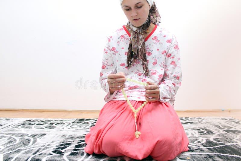 Μια νέα μουσουλμανική γυναίκα εκτελεί την προσευχή στο μουσουλμανικό τέμενος στοκ εικόνες