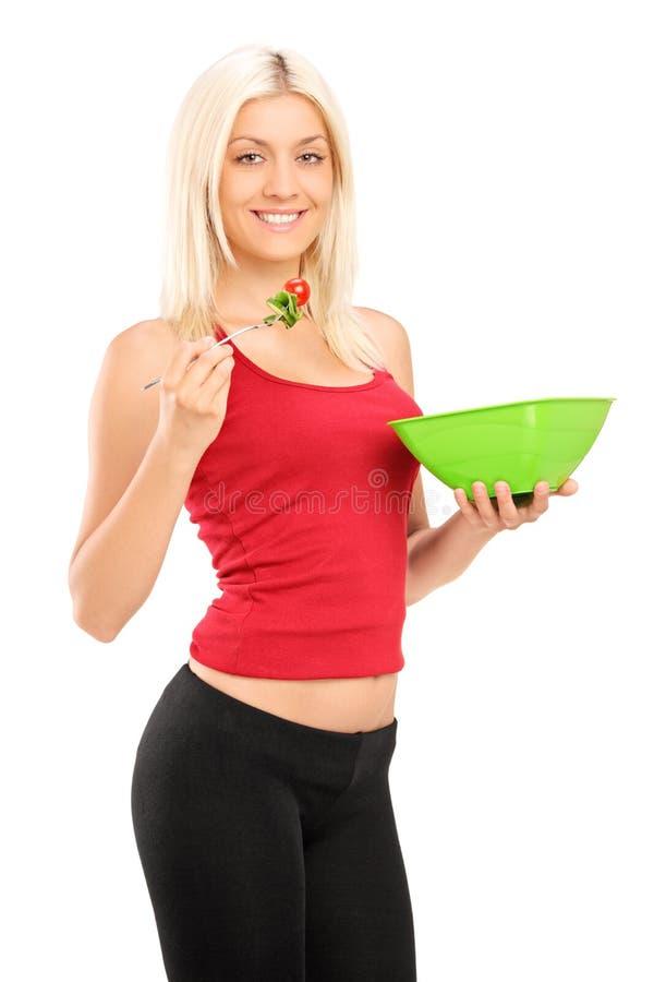 Μια νέα ξανθή γυναίκα που τρώει μια σαλάτα στοκ εικόνες