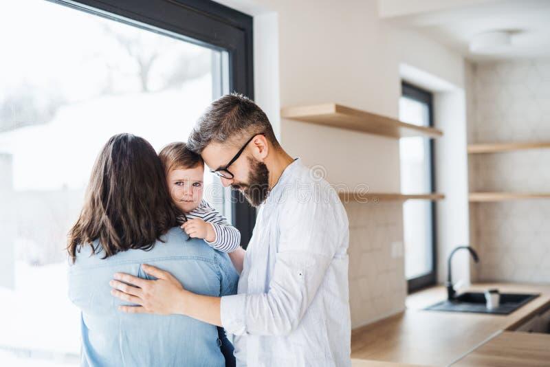 Μια νέα οικογένεια με ένα κορίτσι μικρών παιδιών που στέκεται στο εσωτερικό στο σπίτι στοκ φωτογραφία