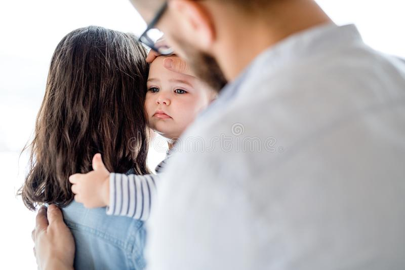 Μια νέα οικογένεια με ένα φωνάζοντας κορίτσι μικρών παιδιών που στέκεται στο εσωτερικό στο σπίτι στοκ φωτογραφία