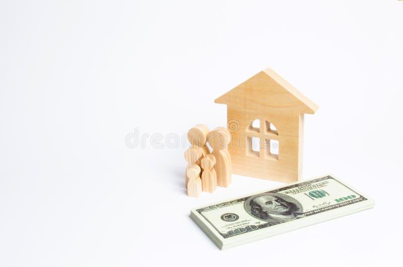 Μια νέα οικογένεια στέκεται κοντά σε ένα ξύλινο σπίτι και με μια δέσμη των χρημάτων Η έννοια μιας ισχυρής οικογένειας στοκ φωτογραφίες με δικαίωμα ελεύθερης χρήσης