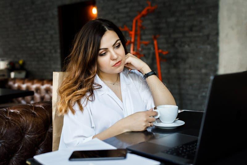 Μια νέα, συμπονετική γυναίκα, όχι ένα λεπτός-διευθυνμένο κτήριο σωμάτων, κάθεται σε έναν άνετο καφέ, εργάζεται σε έναν υπολογιστή στοκ φωτογραφία με δικαίωμα ελεύθερης χρήσης