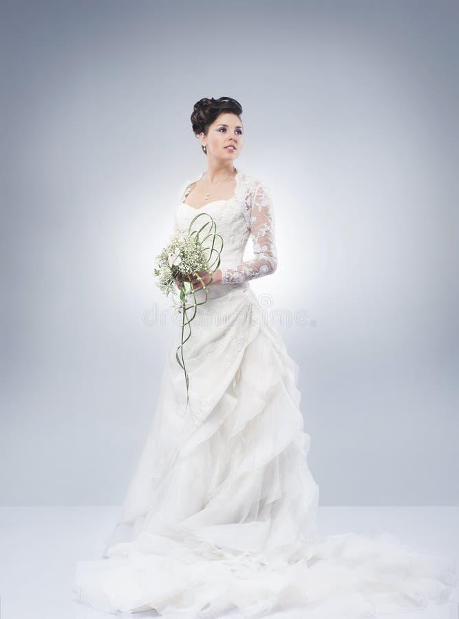 Μια νέα τοποθέτηση νυφών brunette σε ένα άσπρο φόρεμα στοκ εικόνες