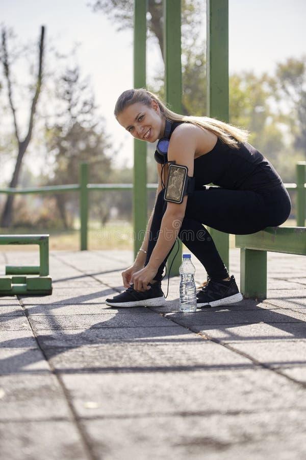 Μια νέα χαμογελώντας γυναίκα, δένοντας κορδόνια, υπαίθρια γυμναστική στο πάρκο, στοκ φωτογραφίες με δικαίωμα ελεύθερης χρήσης