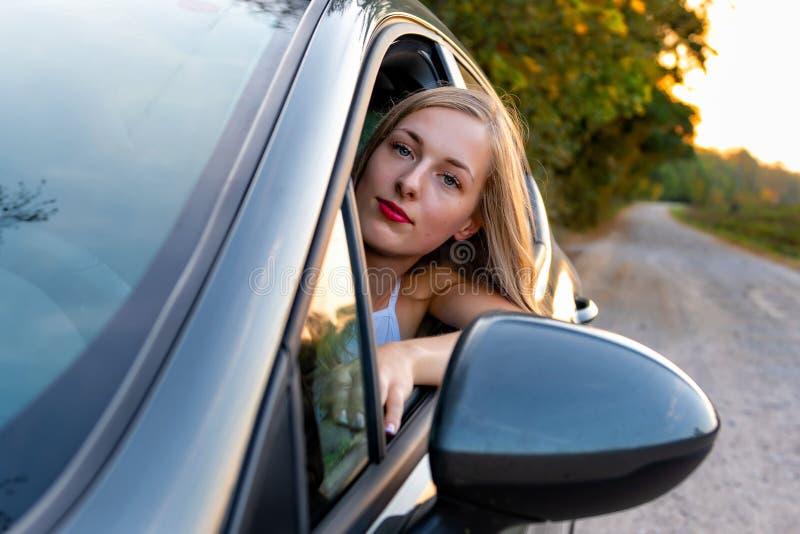 Μια νέα, όμορφη γυναίκα με μακρυμάλλη κάθεται στη ρόδα του αυτοκινήτου και φαίνεται έξω το παράθυρο στοκ φωτογραφίες με δικαίωμα ελεύθερης χρήσης