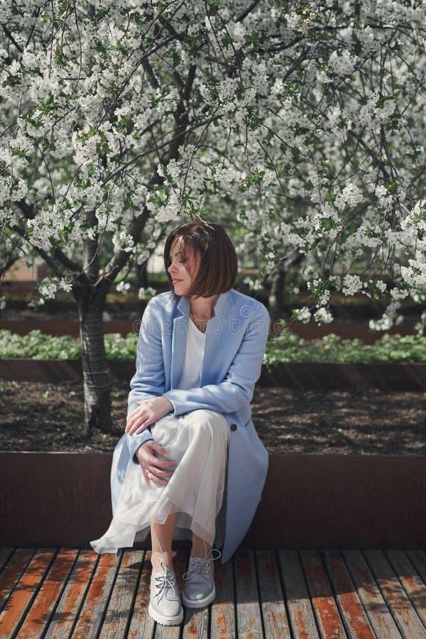 Μια νέα όμορφη γυναίκα brunette με την κοντή τρίχα στα φωτεινά ρομαντικά ενδύματα και ένα μπλε παλτό κάθεται σε έναν πάγκο σε ένα στοκ εικόνες