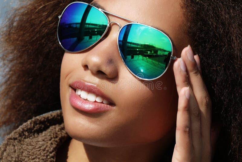Μια νεαρή αφρικανή κοπέλα με γυαλιά ηλίου, που ποζάρει σε εξωτερικό χώρο, ντυμένη περιστασιακά, με κοντά ογκώδη μαλλιά στοκ φωτογραφίες