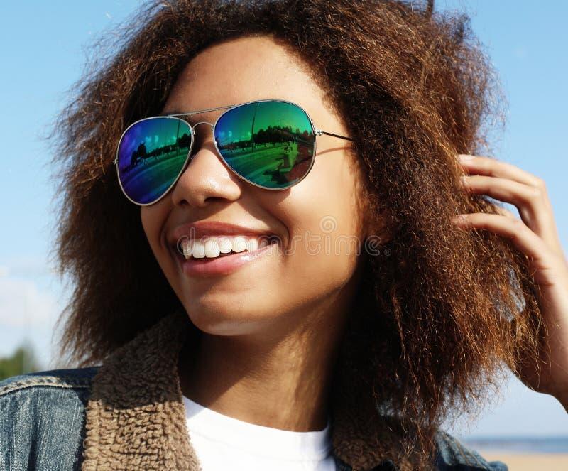 Μια νεαρή αφρικανή κοπέλα με γυαλιά ηλίου, που ποζάρει σε εξωτερικό χώρο, ντυμένη περιστασιακά, με κοντά ογκώδη μαλλιά στοκ εικόνες