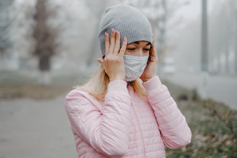 Μια νεαρή γυναίκα στέκεται κοντά στο δρόμο με μια ιατρική μάσκα κρατώντας το κεφάλι της με τα χέρια της Πονοκέφαλος το χειμώνα στ στοκ φωτογραφία με δικαίωμα ελεύθερης χρήσης