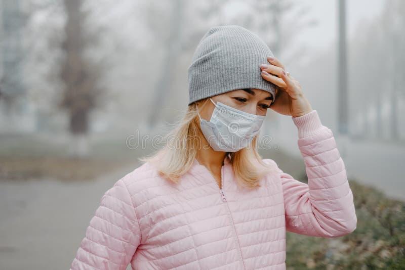 Μια νεαρή γυναίκα στέκεται κοντά στο δρόμο με μια ιατρική μάσκα κρατώντας το κεφάλι της με τα χέρια της Πονοκέφαλος το χειμώνα στ στοκ εικόνα με δικαίωμα ελεύθερης χρήσης