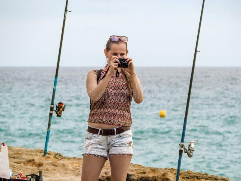 Μια νεαρή ενήλικη γυναίκα με κάμερα στέκεται ανάμεσα σε δύο καλάμια ψαρέματος κοντά στη θάλασσα στοκ φωτογραφίες με δικαίωμα ελεύθερης χρήσης