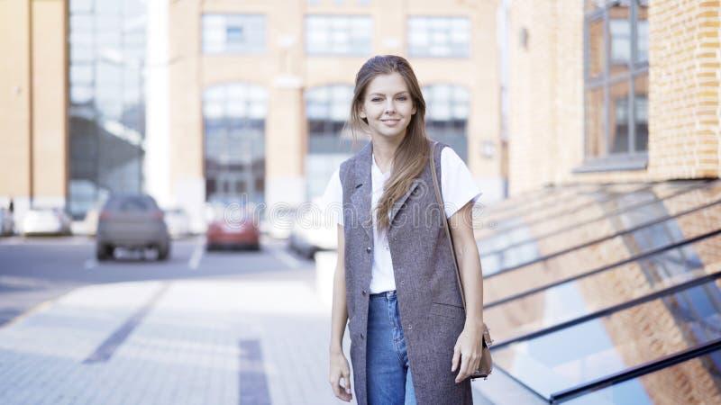 Μια νεολαία που χαμογελά το περιστασιακό κορίτσι στέκεται το εξωτερικό κοιτάζοντας στη κάμερα στοκ φωτογραφία με δικαίωμα ελεύθερης χρήσης