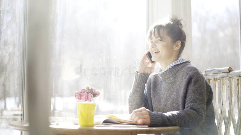 Μια νεολαία που χαμογελά το χαριτωμένο κορίτσι brunette έχει μια κλήση στον καφέ στοκ φωτογραφία με δικαίωμα ελεύθερης χρήσης