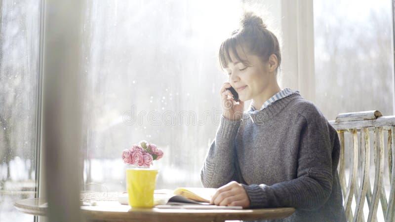Μια νεολαία που χαμογελά το χαριτωμένο κορίτσι brunette έχει μια κλήση στον καφέ στοκ εικόνα