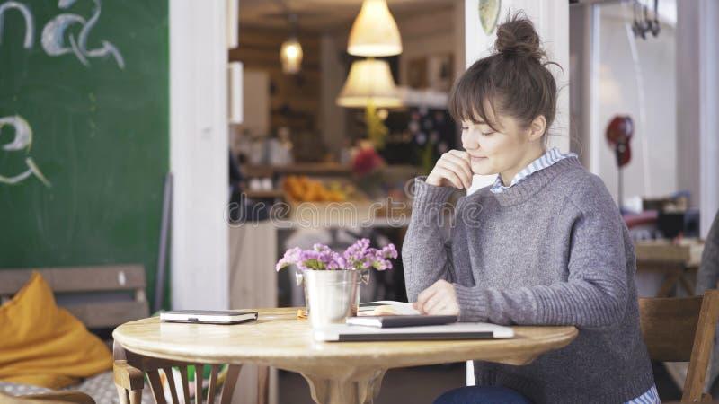 Μια νεολαία που χαμογελά το χαριτωμένο κορίτσι brunette διαβάζει ένα βιβλίο σε έναν καφέ στοκ φωτογραφίες με δικαίωμα ελεύθερης χρήσης