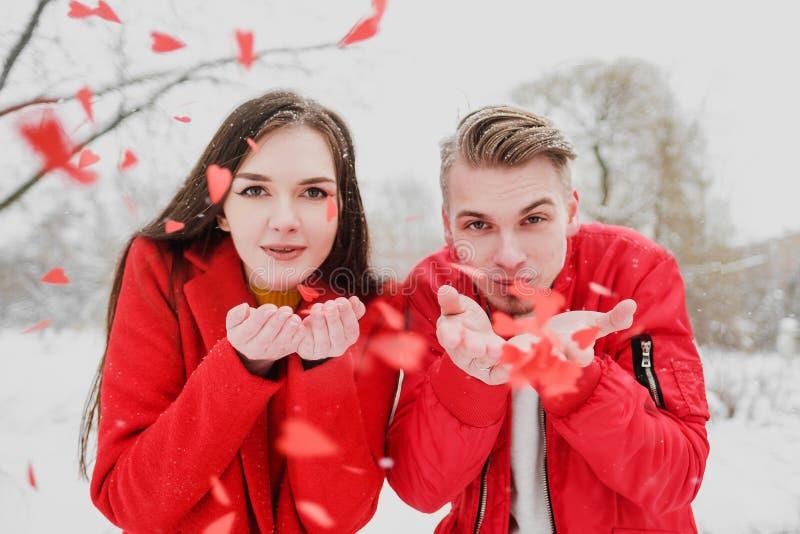 Μια νεολαία συνδέει, ένας τύπος και ένα κορίτσι, υπαίθρια το χειμώνα στα κόκκινα ενδύματα που φυσούν στο κομφετί υπό μορφή καρδιώ στοκ φωτογραφίες